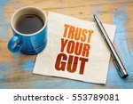 Small photo of Trust your gut word abstract - advice or motivational reminder on a napkin with cup of espresso coffee