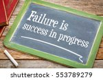 Small photo of Failure is success in progress - inspirational text on a slate blackboard with a white chalk and a stack of books against rustic wooden table