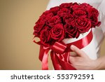 Stock photo man in white t shirt holding in hand rich gift bouquet of red roses composition of flowers in a 553792591
