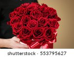 Stock photo man in black t shirt holding in hand rich gift bouquet of red roses composition of flowers in a 553795627