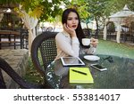 Small photo of Charming woman with beautiful smile is looking at the camera during holding a cup of hot coffee. Copy space for your text message or informative content.