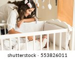 mother putting baby to sleep at ... | Shutterstock . vector #553826011