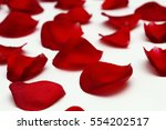 Stock photo bright red rose petals on a white wooden table 554202517