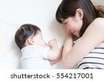 mother and her baby lying on a... | Shutterstock . vector #554217001