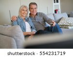 senior couple sitting in couch... | Shutterstock . vector #554231719