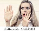young woman in fear raised her... | Shutterstock . vector #554243341