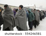 Small photo of Belgrade, Serbia - January 10, 2017: A migrant eats free food during a snowfall outside warehouse. Migrant have occupied an abandoned customs warehouse in Belgrade as they seek ways to move to EU.