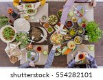 friends having vegetarian feast ... | Shutterstock . vector #554282101