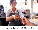 cashier accepts card payment... | Shutterstock . vector #554327725