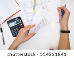 accountant with reports on table | Shutterstock . vector #554331841
