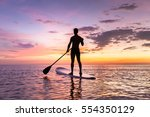 person stand up paddle boarding ...