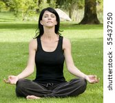 woman doing yoga meditation in outdoor park setting, nice green grass background - stock photo
