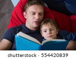 father reading a story to his... | Shutterstock . vector #554420839