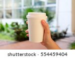 a white cup of coffee in hand