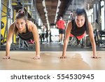 two sporty girls doing push ups ... | Shutterstock . vector #554530945