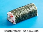 Small photo of Close up of uncut Futomaki sushi roll in nori on blue surface