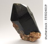 Small photo of Black quartz large crystal on a light background. Morion. For collections of geologists and mineralogists.