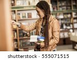 young african woman buying... | Shutterstock . vector #555071515
