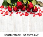 Stock photo red roses with hearts on a old wooden table 555096169