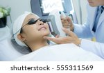 laser machine.young woman... | Shutterstock . vector #555311569
