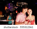 couple with drinks  looking at... | Shutterstock . vector #555312361