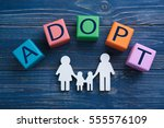 Small photo of Cubes with word ADOPT and figure in shape of family on color wooden background