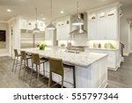 Stock photo white kitchen design features large bar style kitchen island with granite countertop illuminated by 555797344