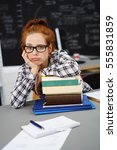 Small photo of Redhead feels overwhelmed with school work rests one arm on a stack of books and pouts