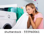 woman smelling clean clothes... | Shutterstock . vector #555960061