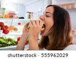 young woman eating delicious... | Shutterstock . vector #555962029