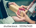 man hands giving gift box to... | Shutterstock . vector #555967435