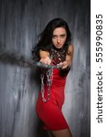 Small photo of Portrait of alluring young woman in red short dress posing with chains