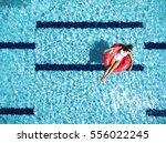woman relaxing on donut lilo in ... | Shutterstock . vector #556022245