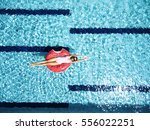woman relaxing on donut lilo in ... | Shutterstock . vector #556022251