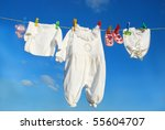 Stock photo baby clothes and accessories hanging on clothesline against blue sky 55604707