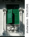Small photo of Contrasting green window with louvers ajar shophouses old architecture along streets of Southeast Asia Singapore Malaysia commercial buildings