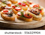 Small photo of Crostini with different toppings on wooden background. Delicious appetizers. Front view.