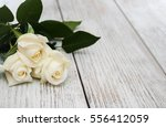 Stock photo white roses on a old white wooden table 556412059