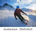 Skier on piste in high mountains with beautiful sky on sunny day. Active downhill ride. - stock photo