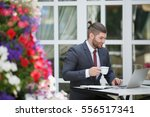 Small photo of Side view shot of handsome smiling business man in formal suit working with laptop while sitting at the wooden table outdoors and enjoying morning coffee