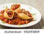 Small photo of Italian pasta Conchiglioni Rigati stuffed with dry tomatoes and meat. Sprinkled with cheese. Front view.