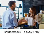 young female barista serving... | Shutterstock . vector #556597789