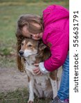 Small photo of Young caucasian girl hugging Shiba Inu dog on meadow in winter season. The kid is showing her affection to the loyal animal that is part of the family.