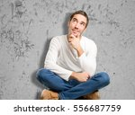 seated young man wondering | Shutterstock . vector #556687759
