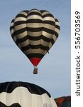 Small photo of A black and white stripey hot air balloon rising above another balloon