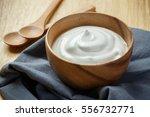 plain yogurt in wooden bowl on... | Shutterstock . vector #556732771