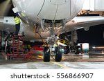 Stock photo pre flight service of modern passenger aircraft in the night airport the main landing gear close 556866907