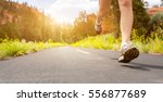 legs in sport shoes on road at... | Shutterstock . vector #556877689