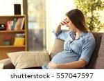 worried pregnant woman sitting... | Shutterstock . vector #557047597