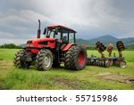 Red Tractor Parked On A Grass...